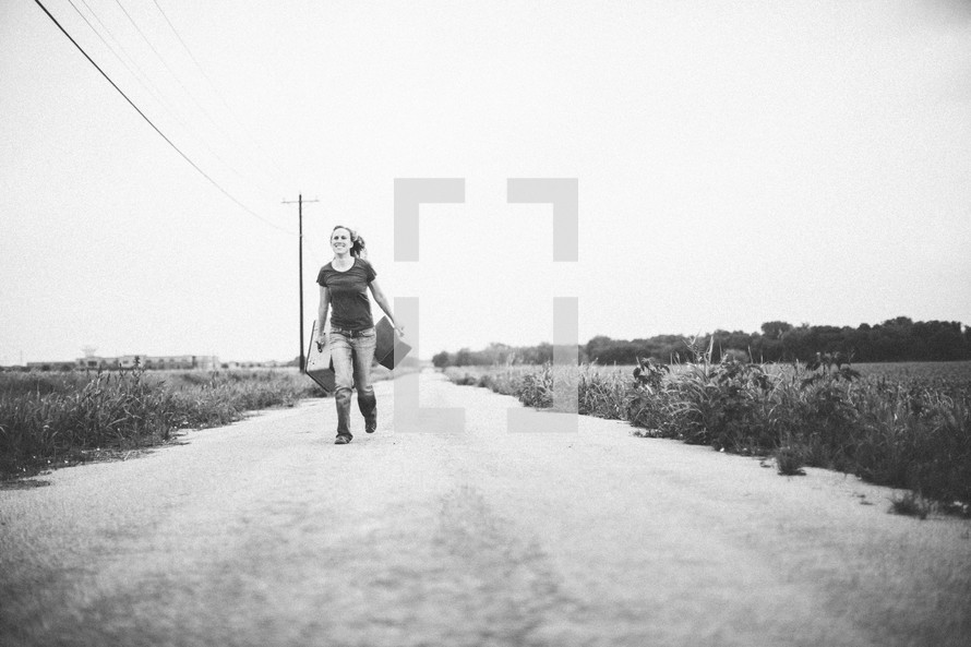 woman running down a road carrying suitcases