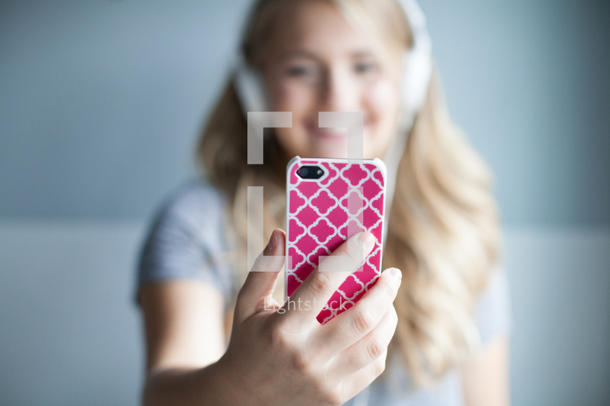 blonde woman listening to music on her iPhone