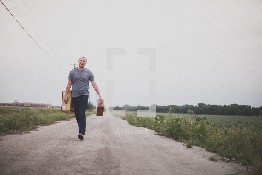 man carrying suitcases walking down a road