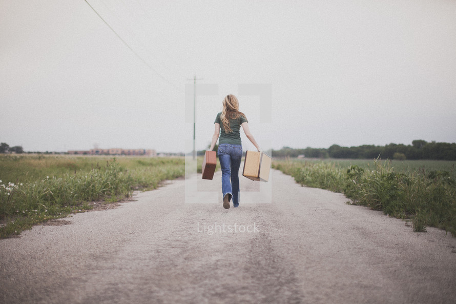 woman walking down the middle of a road carrying suitcases