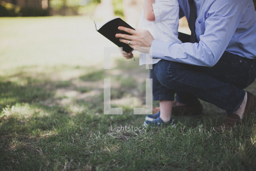 father reading a Bible to his son