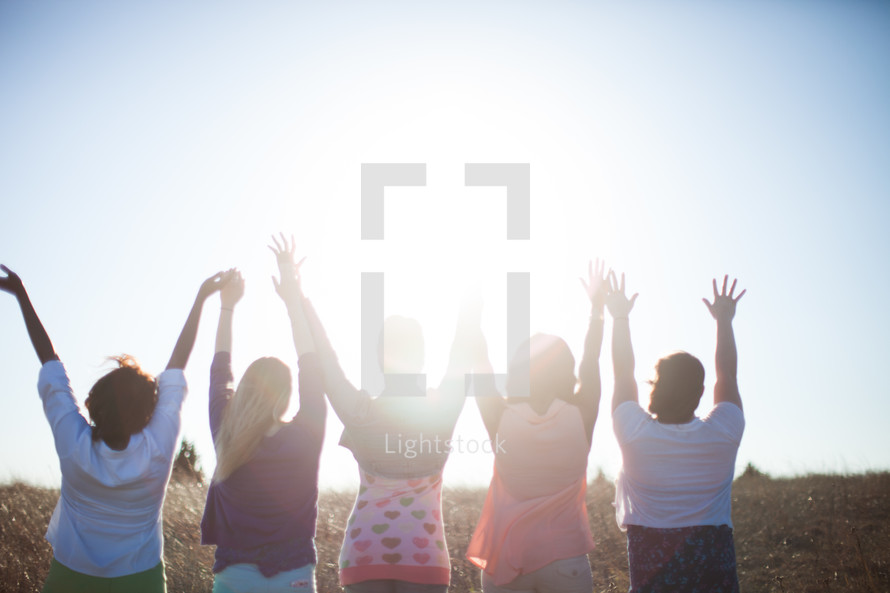 women with raised hands outdoors in a field