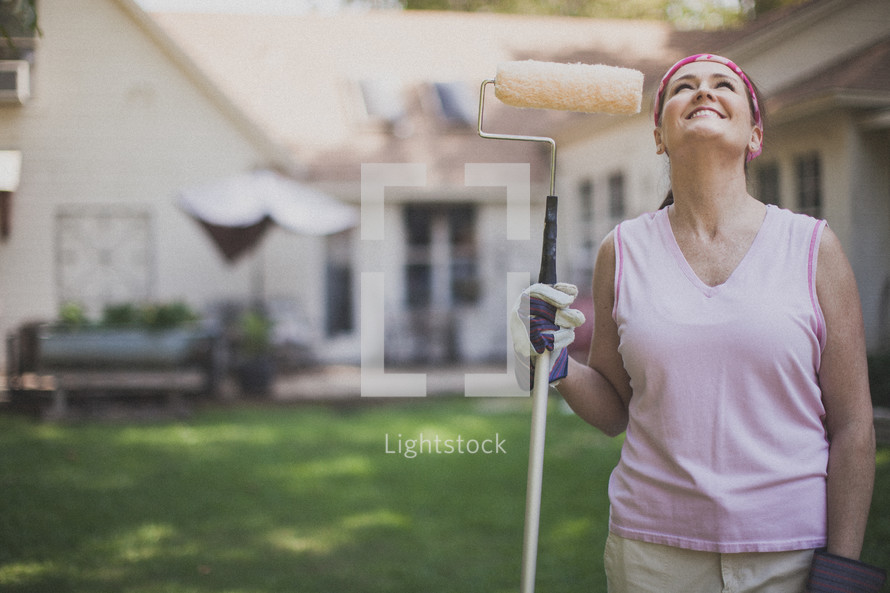 woman holding a paint roller and looking up to God