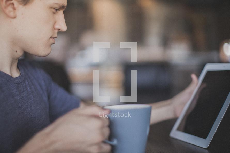 man reading on an iPad