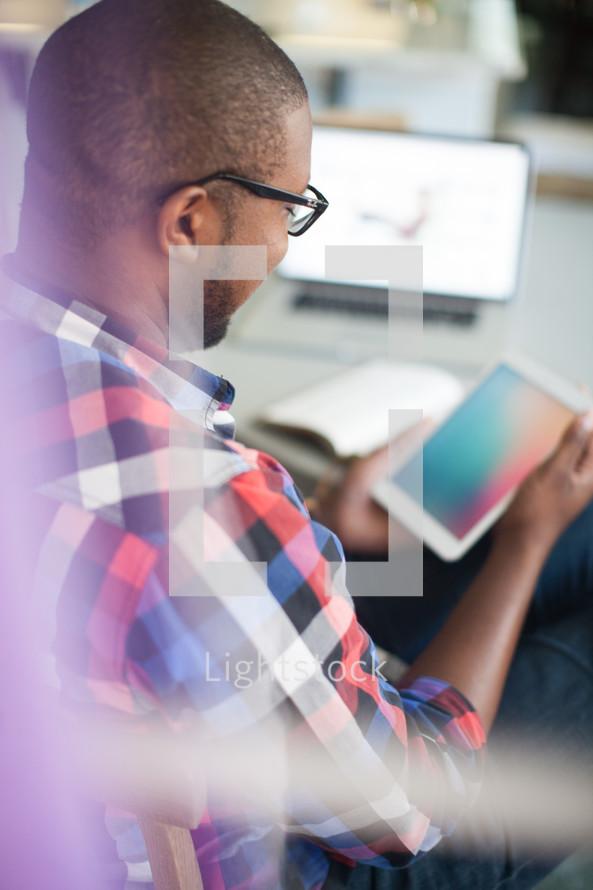 man looking at am iPad screen