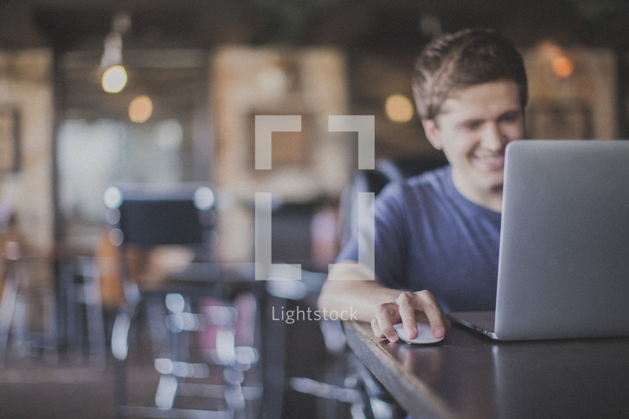 man working at a laptop in a coffee shop