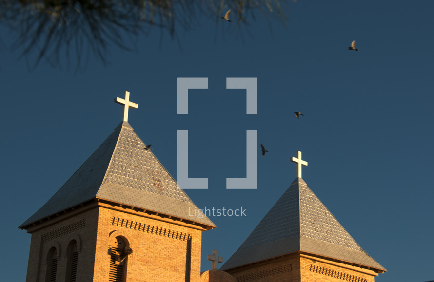 peaks of church roof with cross toppers