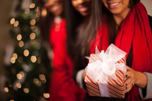 three African American women holding Christmas gifts