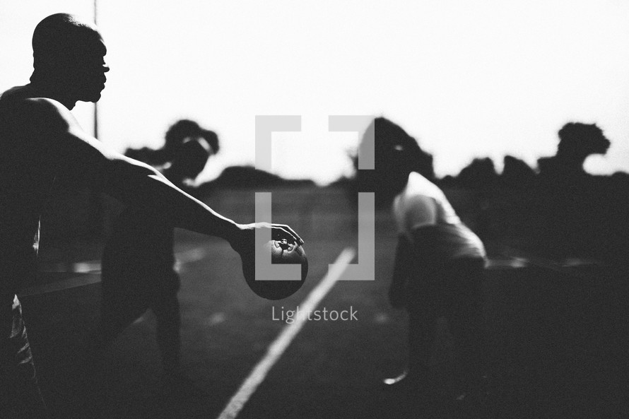 Silhouette of men playing football.