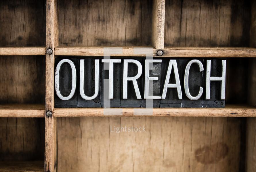 word outreach in blocks on a bookshelf