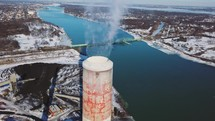 Massive functional smokestacks by giant river and steel bridge.