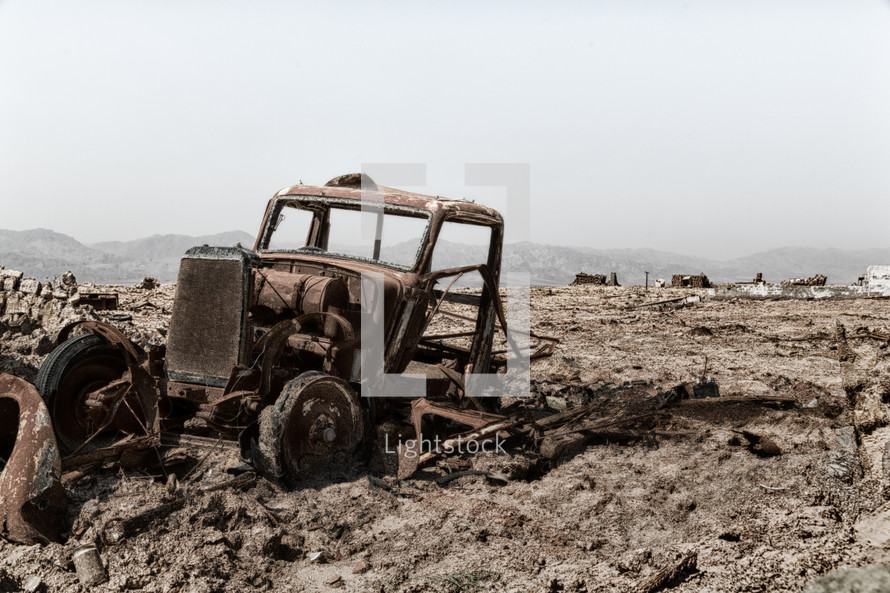 old rusted out truck in a desert