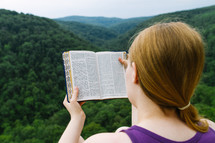 woman reading a Bible on a mountaintop