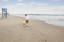 Grandmother and grandson walking along the beach.