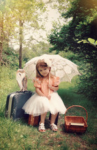 a little girl with a parasol sitting in the woods with luggage and an owl