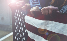 hands holding the edge of an American flag