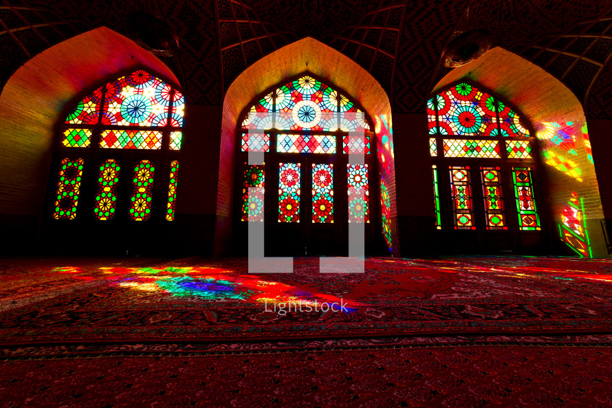 light from stained glass windows shining onto rugs