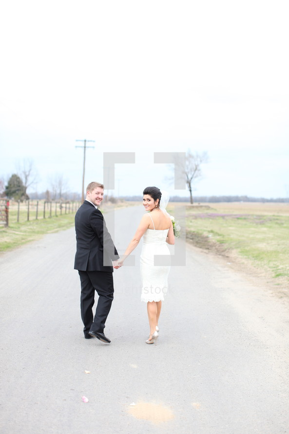 bride and groom holding hands walking down a country road