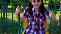 Little girl smiling on a swing in summer park