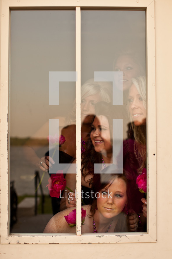 bridesmaids looking out a window
