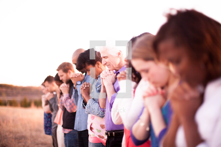 group of people with heads bowed and praying hands outdoors