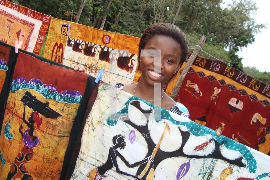 African girl smiling behind artwork at a batik market
