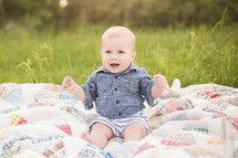 an infant boy sitting on a blanket in the grass