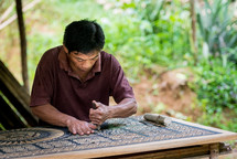 a man carving ornate detail into wood
