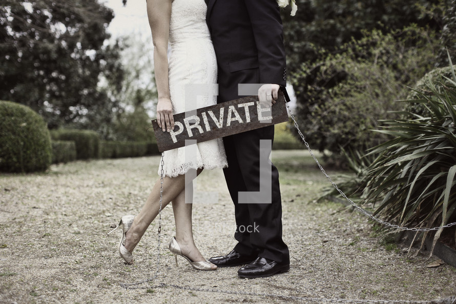 torso of bride and groom holding a private sign