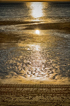 sunlight reflecting on wet sand on a beach