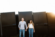 a couple holding hands in front of a metal wall
