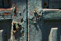 rusty door hinges oom a green wood door
