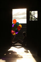 a teen girl sitting with balloons