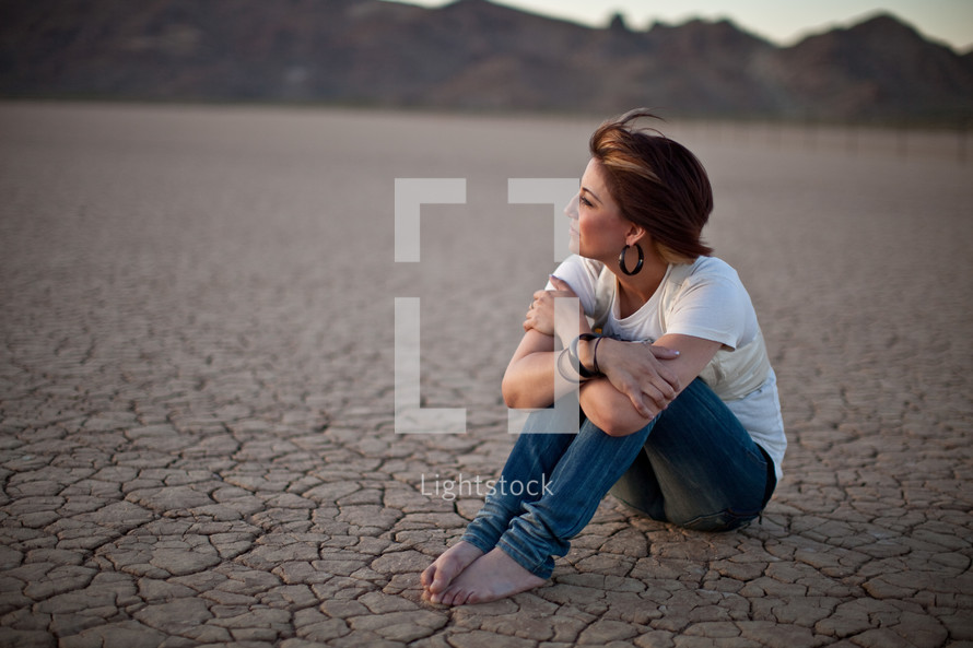 woman sitting on parched ground