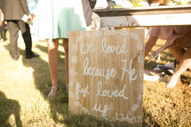 we loved because he first loved us sign at a wedding reception