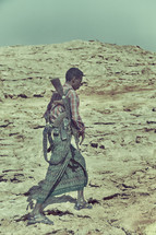 a man carrying a rifle along the African border