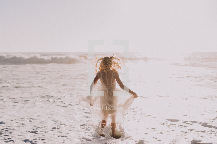 a woman in a flowing sheer dress standing in the ocean
