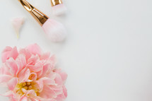pink spring flowers and makeup brush on a white background