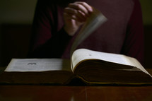 a man turning the pages of a Bible