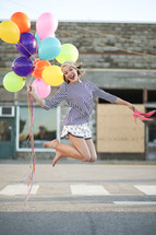teen girl jumping holding balloons and shoes