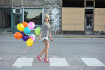 Woman in a hat and high heels walking down the street holding balloons.