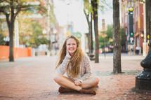 a young woman sitting on a brick sidewalk