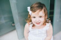 face of a little girl standing in front of a door