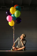 a teen girl sitting on the floor with balloons