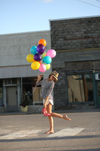 teen girl carrying balloons and her shoes