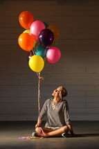 a woman holding balloons sitting on the floor