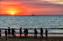people on the bay of Darwin watching the sunset