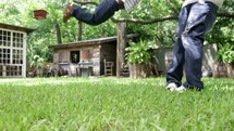 A father swinging his young son around and around in the back yard.
