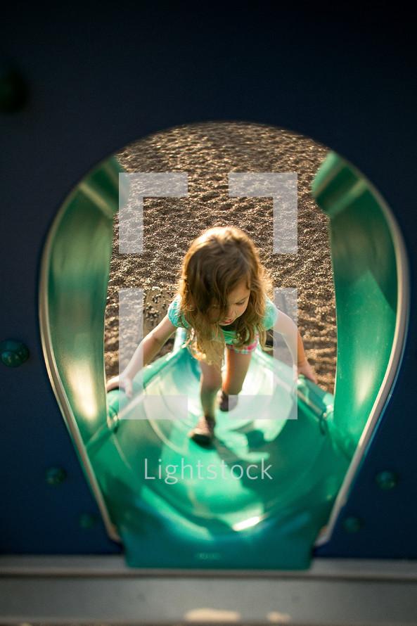 Girl climbing playground slide