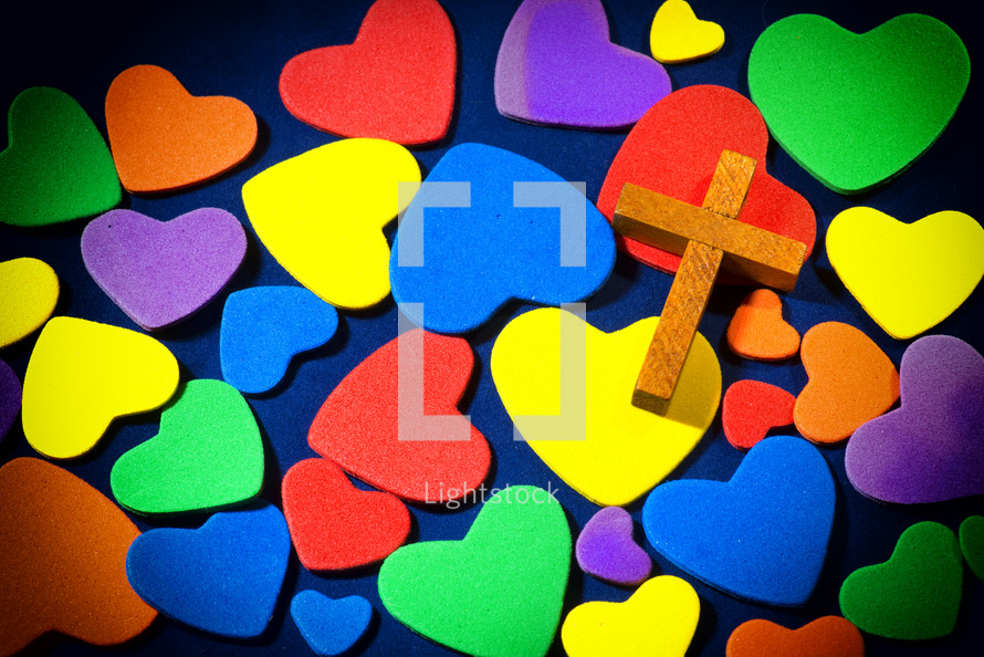 Wooden cross on colorful hearts.